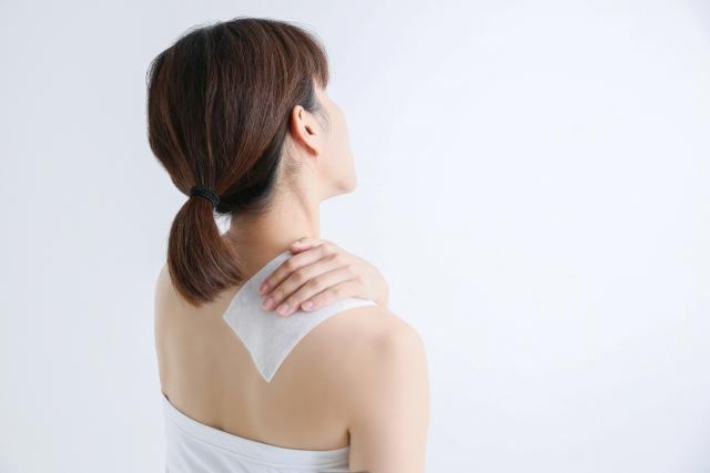 寝違えで肩が痛み湿布を貼る女性の画像